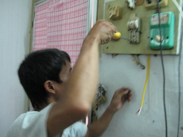 Kỹ thuật viên điện nước Hà Nội đang kiểm tra 1 ổ điện tại nhà khách hàng